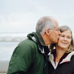 Older man kissing the cheek of older woman on the beach