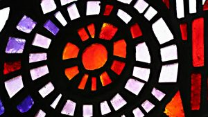 Image of abstract stained glass window with red, white, and blue panes of glass, religious and spiritual