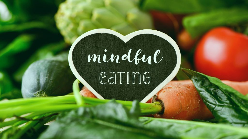 photo of a vegetables including a carrot, tomato, artichoke and there is a heart with the words Mindful Eating