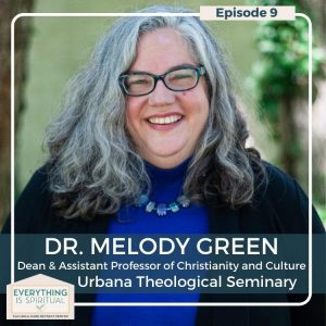 Dr. Melody Green, Dean of Urbana Theological Seminary, headshot showing smiling woman with grey shoulder-lenght hair and glasses in a black suit with blue shirt