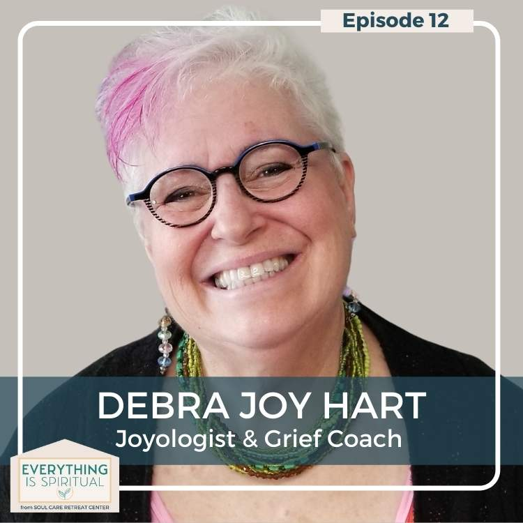 selfie of Debra Joy Hart, she has white short hair with a pink streak, round glasses, and a big smile